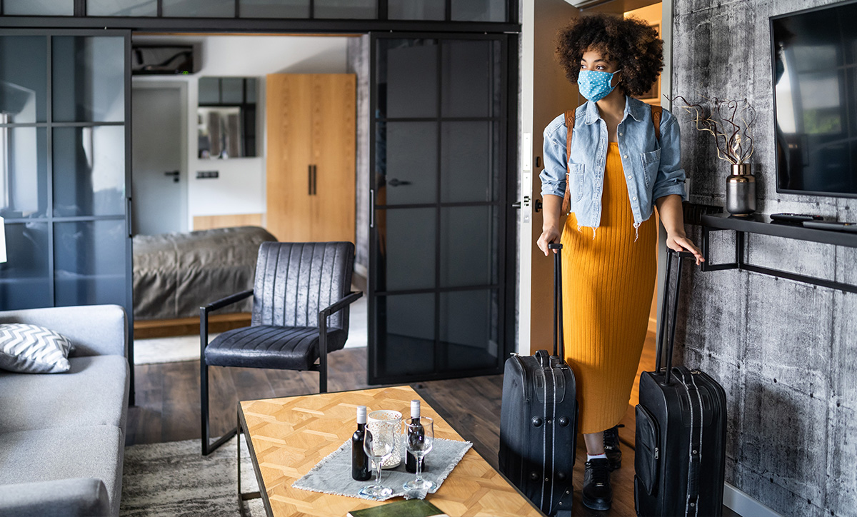 Covid-savvy woman entering her hotel room with suitcases in tow.